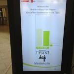 Monitor im Eingangsbereich des Bezirksrathaus in Köln Nippes zur Bürgerinformation über Stromverbrauch in der Meldehalle